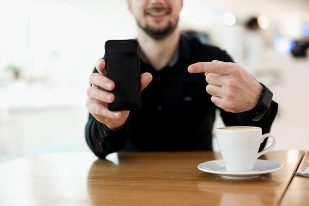 このアプリは蓄積されています!空白のコピースペース画面を備えたスマートフォン。スマートフォンを持ってお気に入りのモバイルアプリを見せてくれる黒ひげの満足男!男性プログラマーはクールなアプリケーションを開発しました。