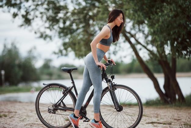 Questa bici è bella. ciclista femminile con una buona forma del corpo in piedi con il suo veicolo sulla spiaggia durante il giorno