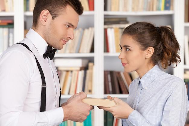 이 책은 제 것입니다! 한 권의 책을 함께 들고 도서관에 서 있는 동안 서로를 바라보는 젊은 괴상한 부부