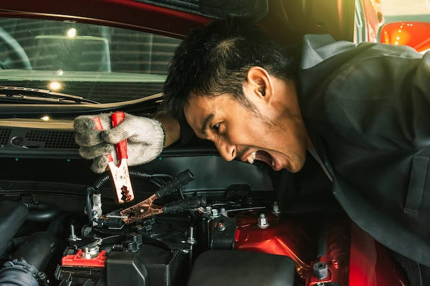 This career inspection asian man car service charging battery car