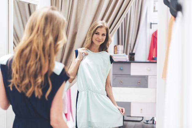이 드레스는 완벽합니다! 드레스를 입고 매장의 피팅룸에 서서 거울에 비친 자신의 모습을 바라보는 아름다운 젊은 여성의 뒷모습