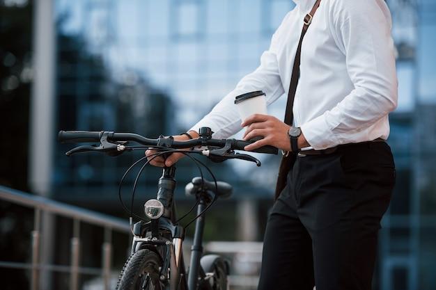 이 남자는 차가 필요하지 않습니다. 검은 자전거와 공식적인 옷을 입은 사업가가 도시에 있습니다.