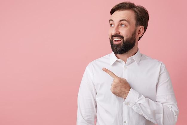 この男は素晴らしいニュースを持っています!大きく笑って、ピンクの背景の上に隔離された左側のコピースペースを指してあなたの注意を引きます。