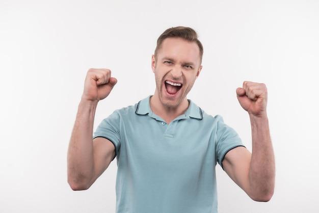 これは成功です。彼の成功を祝いながら拳を握り締めるうれしそうな前向きな男