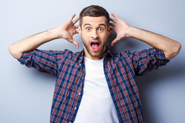 Это потрясающе! удивленный молодой человек в повседневной рубашке держит рот открытым и смотрит в камеру, стоя на сером фоне