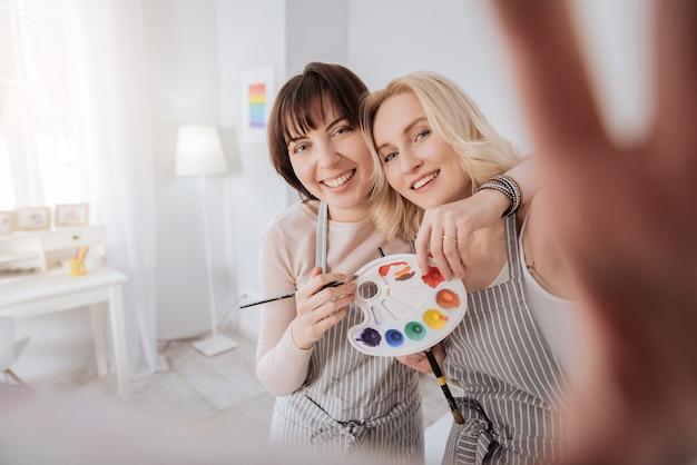 それはアートです。彼女のガールフレンドと一緒に立って、写真を撮っている間カメラを持っているポジティブな創造的な若い女性