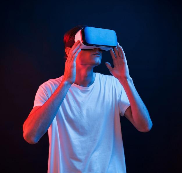 Это захватывает дух. молодой человек в очках виртуальной реальности в темной комнате с неоновым освещением
