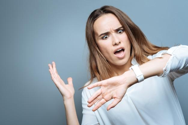 이것은 비극적입니다. 불행한 예쁜 젊은 여자가 그녀의 시계를보고 시간을 확인하는 동안 충격을 받고