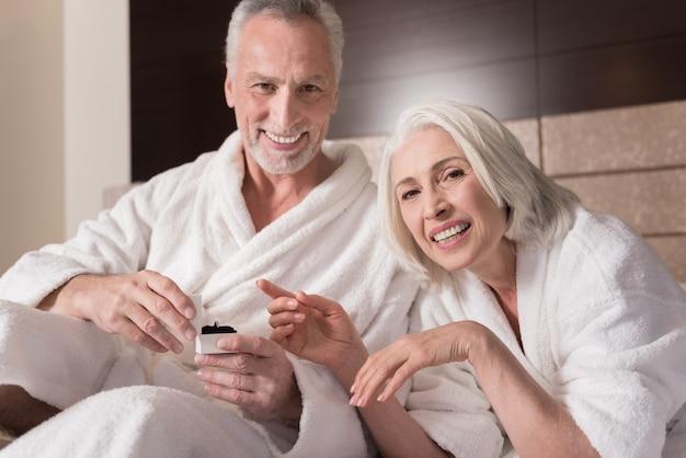 이건 널위한거야. 침대에 누워 행복을 표현하는 동안 그의 여자에게 반지를주는 명랑 웃는 세 남자