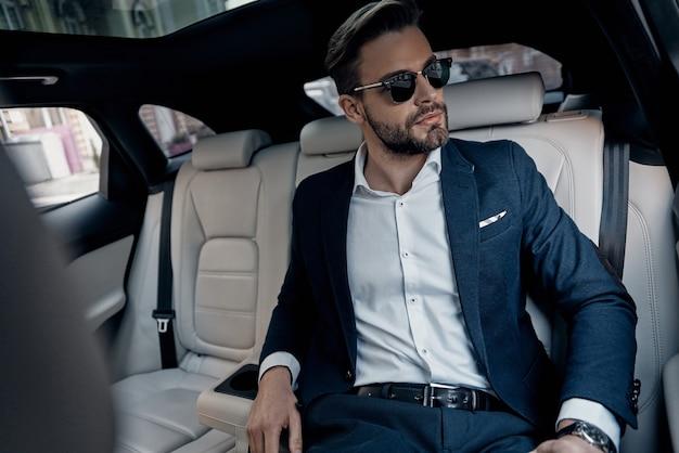 이것은 긴 하루가 될 것입니다. 차에 앉아있는 동안 멀리보고 전체 양복에 잘 생긴 젊은 남자