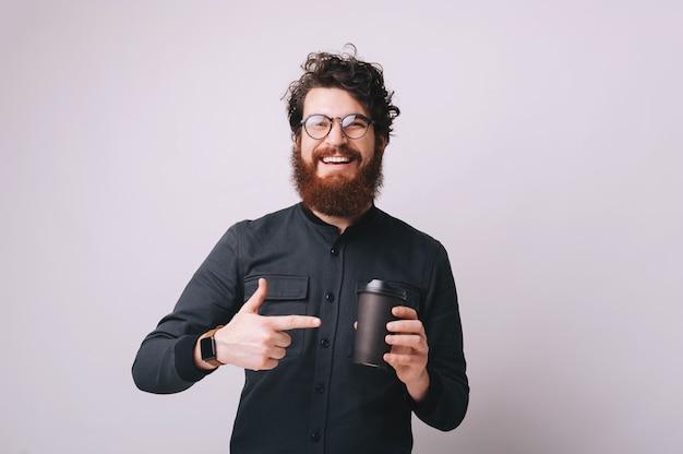これはいい。眼鏡をかけて、コーヒーとカップを指して、孤立した背景の上に立っているハンサムなひげを生やした男