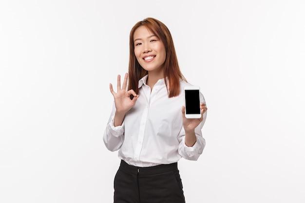 これはいい。携帯電話のディスプレイを示す満足のいく見栄えの良いアジアの女性、大丈夫なジェスチャーを作る、優れたアプリを評価する、クールな写真を撮ることを誇りに思う、白い壁に立っている