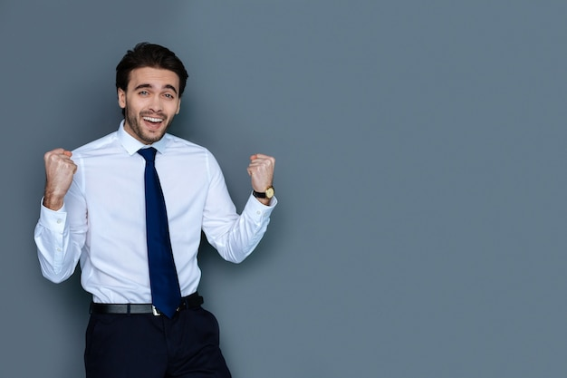 これは素晴らしい。あなたを見て、彼の成功を祝いながら笑っているうれしそうな素敵な喜んでいる男