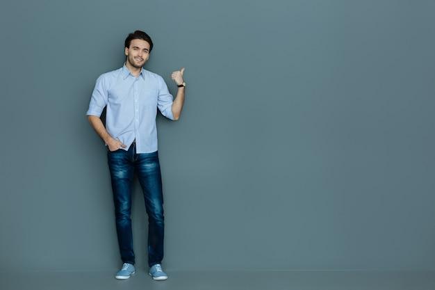 こちらです。ポケットに片手を入れて、あなたを見ながら指で指している陽気なポジティブなナイスマン