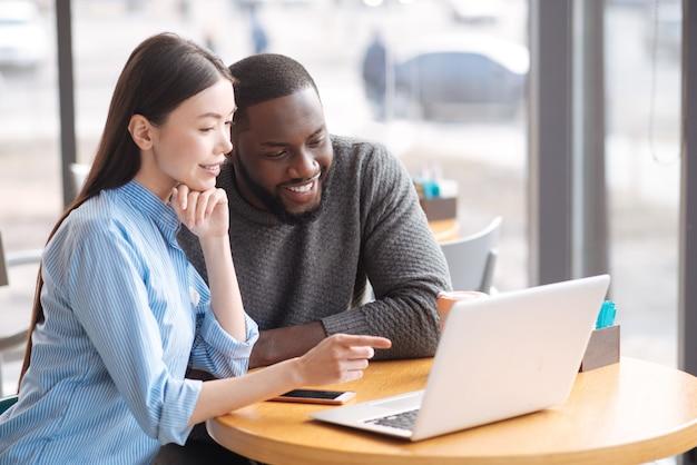 これです。彼女の幸せな男性の友人の近くのカフェテリアに座っている間ラップトップを指しているかなり若い笑顔の女性。