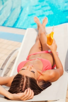 This is the life. top view of beautiful young woman in bikini holding cocktail while relaxing in deck chair by the pool