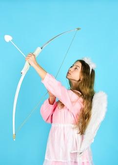 이것은 사랑입니다. 사랑과 로맨스. 행복한 발렌타인 데이. 사랑을 축하합니다. 발렌타인 판매 및 할인. 천사 의상을 입은 아이. 작은 천사. 소녀 큐피드 활과 화살을 잡으십시오. 큐피드 화살이 바로 마음에 맞았습니다.