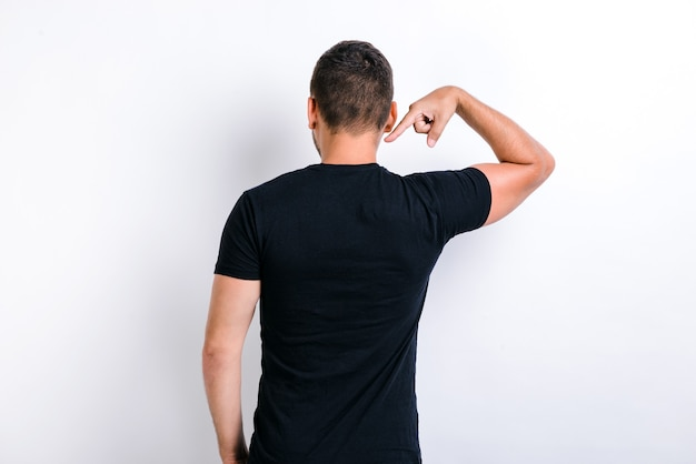 This is me. back view of proud handsome young man standing and pointing at himself. indoor studio shot, isolated on white background