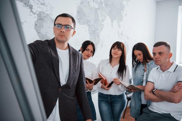 これが今後数か月の戦略です。教室で新しいプロジェクトに取り組んでいるビジネスマンとマネージャー