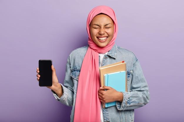 이것은 당신이 필요로하는 전화입니다. 이슬람 전망을 가진 즐거운 여성, 전통 히잡 착용, 스마트 폰 화면 표시 및 웃음