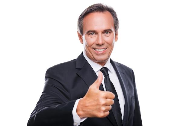 이것은 성공이다! 흰색 배경에 엄지손가락을 들고 서 있는 동안 카메라를 보고 웃고 있는 정장 차림의 쾌활한 성숙한 남자