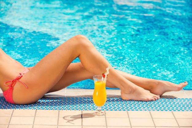 이것이 삶이다. 전경에 칵테일과 함께 수영장에서 아름다운 여성 다리의 측면 보기