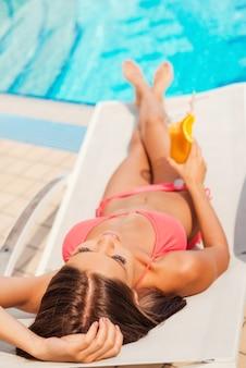 이것이 삶이다. 수영장 옆 갑판 의자에서 휴식을 취하는 동안 칵테일을 들고 비키니를 입은 아름다운 젊은 여성의 상위 뷰