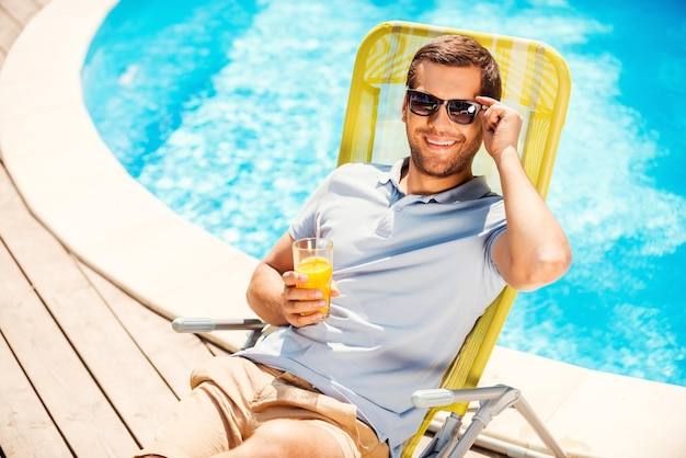 Это жизнь! вид сверху веселого молодого человека в рубашке поло, сидящего на шезлонге и держащего стакан с апельсиновым соком