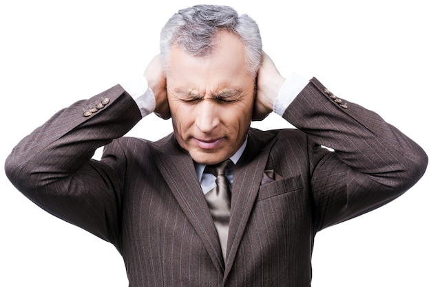 This is too loud! frustrated mature man in formalwear holding head in hands and keeping eyes closed while standing against white background