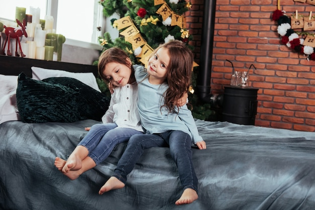 This is truly friendship. kids sits on the bed with decorative background. conception of new year