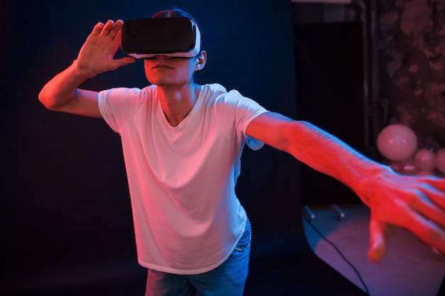 Это невероятно. молодой человек в очках виртуальной реальности в темной комнате с неоновым освещением