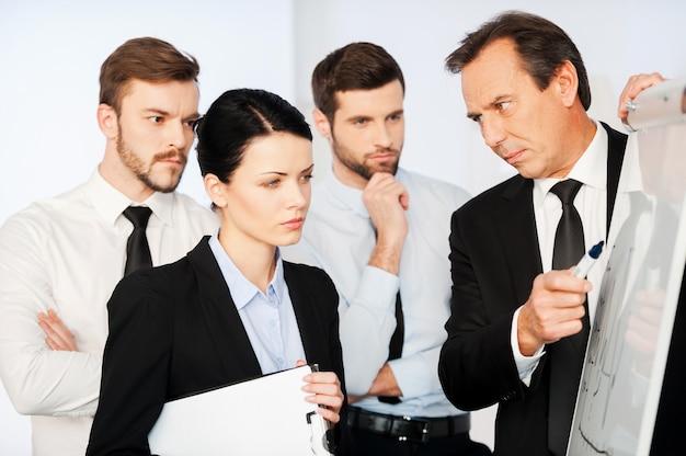 Это очень важно! уверенный зрелый бизнесмен, указывая на график на доске, в то время как его коллеги стоят рядом и смотрят на эскиз