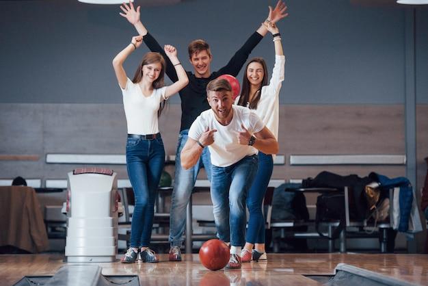 Questa è una vittoria. i giovani amici allegri si divertono al bowling durante i fine settimana