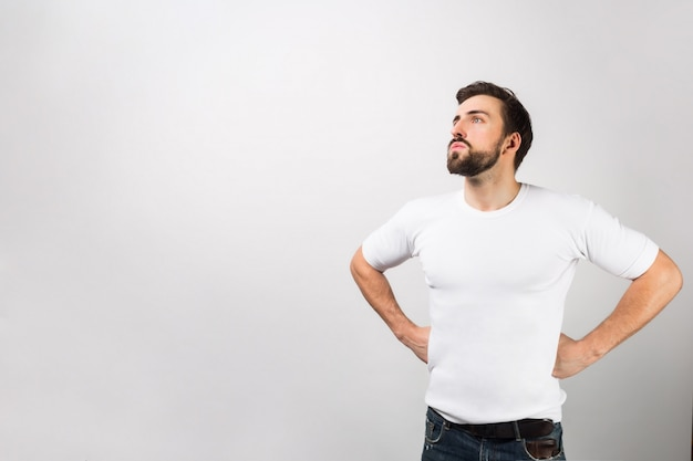 This man is standing in a position of a hero putting his hands on his hips. he is dreaming about better times or the future. that guy looks very serious. isolated on white wall.