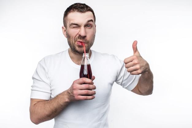 이 남자는 패스트 푸드와 단 음료를 아주 좋아합니다. 그는 기쁨으로 병에서 콜라를 마시고 있습니다. 또한 젊은 남자가 그의 큰 엄지손가락을 들고 있다. 흰색 배경에 고립