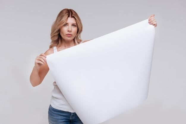 Это важно. преданная изящная серьезная дама принимает участие в новой социальной кампании и держит плакат
