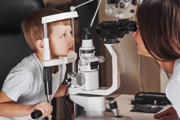 これにはもう1分かかる場合があります。小さな男の子は、女性医師による特別な光学装置で彼の目をテストしています。