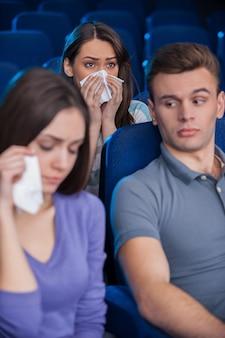 Этот фильм только для женщин. скучно молодой человек сидит вместе с плачущими женщинами во время просмотра фильма в кинотеатре
