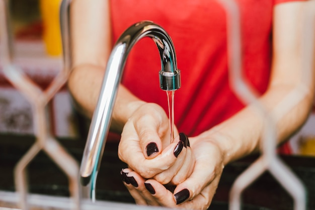 In this photo illustration a woman washes her hands on the faucet.