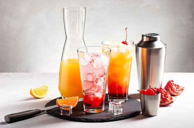 이 사진은 아이스 오렌지 주스로 알코올 칵테일 데킬라 선 라이즈를 만드는 과정을 보여줍니다.
