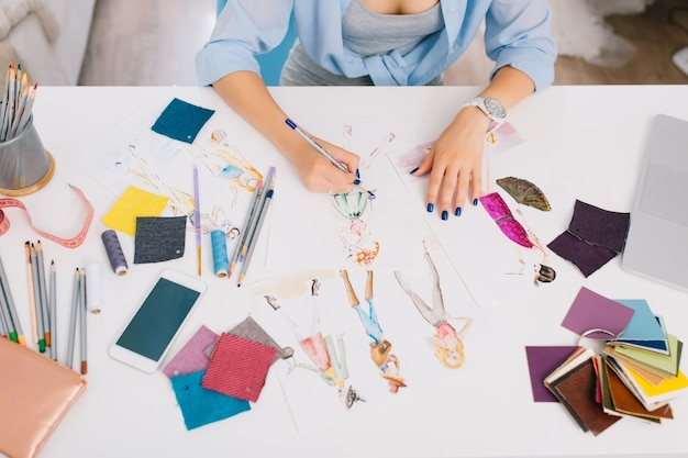 This picture describes the processes of designing clothes. there are hands of a girl drawing sketches on the table. there is creative mess with different stuff on the table.