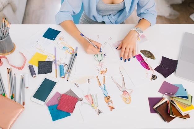 この写真は、服をデザインするプロセスを説明しています。テーブルにスケッチを描いている女の子の手があります。テーブルには、さまざまなものがある創造的な混乱があります。