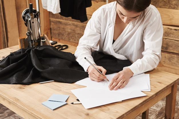 This piece of clothes will be my best. side-angle shot of busy talented sewer creating design of new outfit, standing in her workshop near table with sewing machine and fabric. imagination is key