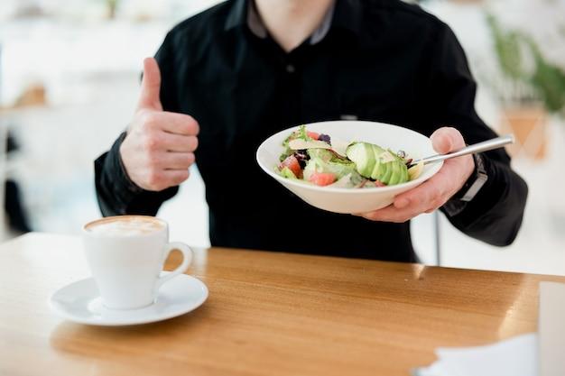 このサラダは本当にいいです。男は親指を立て、魚の緑とアボカドのサラダとプレートを保持します。テーブルの上のおいしいフラットホワイトのカップ。ビューをカットします。健康食品のコンセプト。黒いシャツ。スマートなスタイル。