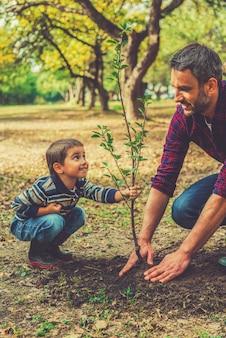 이 나무는 당신과 함께 자랄 것입니다! 정원에서 함께 일하는 동안 아버지가 나무를 심는 것을 돕는 장난기 많은 어린 소년