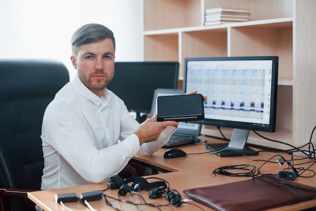 이것은 심문에 매우 도움이 될 것입니다. 거짓말 탐지기 검사관은 거짓말 탐지기 장비를 가지고 사무실에서 일합니다.