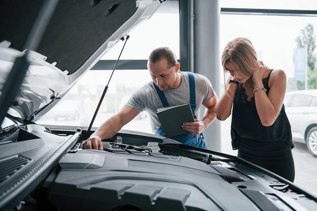 Это не займет много времени. результаты ремонта. уверенный мужчина показывает, какие повреждения получила ее машина