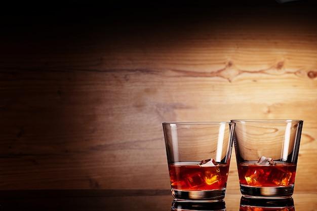 木製の背景の上にウイスキーのグラス