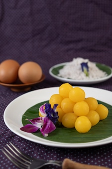 Thong yod dessert on a banana leaf in a white plate with orchids and a fork