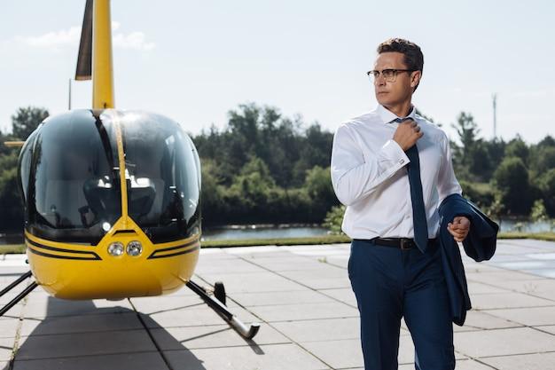 徹底的な検査。新しいヘリコプターの状態を確認した後、ヘリコプターのパッドを歩き回るスーツを着た魅力的な若いceo